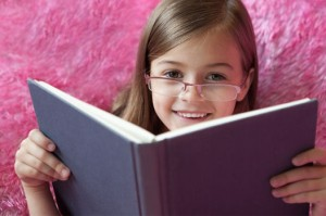 Young girl with glasses reading book