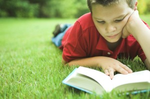 boy reading on grass